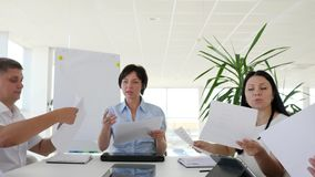 El ejecutivo empresarial con las hojas de papel distribuye las asignaciones para los colegas en la oficina blanca metrajes