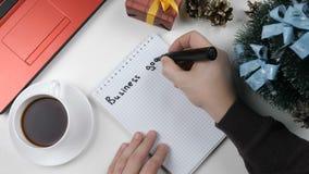 El ejemplo, Año Nuevo, las manos masculinas escribe en un cuaderno, metas 2018 de negocio almacen de video