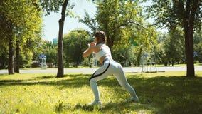 El ejercicio de la mujer joven, haciendo se pone en cuclillas en hierba en parque en ciudad almacen de metraje de vídeo