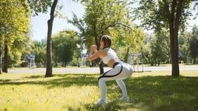El ejercicio de la mujer joven, haciendo se pone en cuclillas en hierba en parque en ciudad metrajes