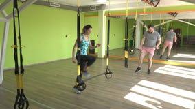 El ejercicio del grupo en el gimnasio moderno en las bisagras del TRX, un hombre y las muchachas juegan los deportes en el gimnas metrajes