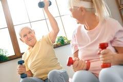 El ejercicio mayor de los pares juntos en casa que hace aeróbicos levanta para arriba la sonrisa de los dubbells Fotos de archivo