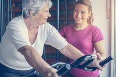 El ejercicio personal del instructor ayuda a la mujer mayor Mujer mayor en el th imagenes de archivo