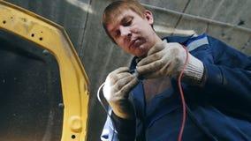 El electricista automotriz comprueba la electro retransmisión en el coche, pequeña empresa - servicio auto del garaje metrajes