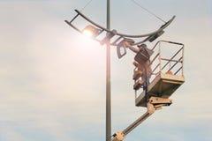 El electricista del funcionario instala un bulbo en una lámpara de calle Profesión que proporciona comodidad, electricidad en ciu fotografía de archivo
