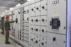 El electricista del ingeniero cambia el equipo del dispositivo de distribución Foto de archivo libre de regalías