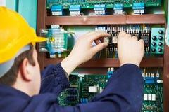 El electricista en el dispositivo del fusible de seguridad substituye el trabajo Foto de archivo libre de regalías
