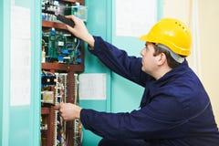 El electricista en el dispositivo del fusible de seguridad substituye el trabajo Fotos de archivo libres de regalías