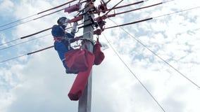 El electricista en equipo sujeta en polo concreto con los pierna-hierros que montan los alambres almacen de video