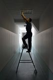 El electricista en la escalera de mano instala la iluminación al techo Imagen de archivo libre de regalías