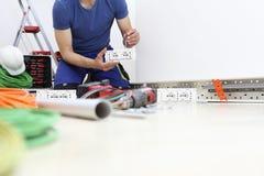 El electricista en el trabajo con destornillador a disposición conecta los cables con el zócalo, circuitos eléctricos, cableado e imagenes de archivo
