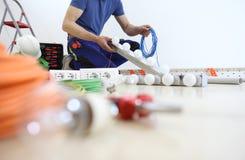 El electricista en el trabajo que instala la lámpara, con el cable a disposición, instala los circuitos eléctricos, cableado eléc imagenes de archivo