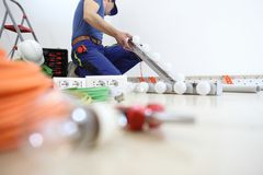 El electricista en el trabajo que instala la lámpara, instala los circuitos eléctricos, cableado eléctrico foto de archivo libre de regalías