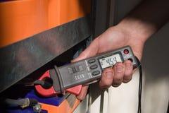 El electricista mide una corriente consumida. Fotografía de archivo
