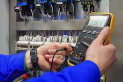 El electricista mide voltaje con el multímetro en gabinete eléctrico Foto de archivo libre de regalías