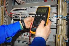 El electricista mide voltaje del circuito eléctrico en el control Ca Fotografía de archivo libre de regalías