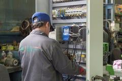 El electricista monta y ajusta el gabinete de control eléctrico Trabajos sobre la junta del circuito eléctrico de a foto de archivo