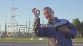 El electricista satisfecho disfruta en éxito Ingeniero y trabajador en la subestación eléctrica Trabajador con la tableta y almacen de video