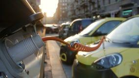 El electro coche está cargando en la calle metrajes