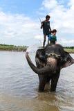 El elefante que toma una ducha con el turista y el conductor en chitwan, Nepal Fotos de archivo