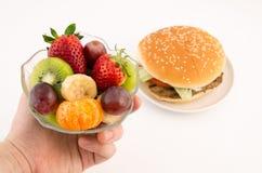 El elegir entre la hamburguesa y las frutas foto de archivo