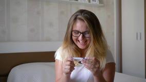 El embarazo inesperado, mujer joven feliz con la prueba del control de la natalidad se sienta al borde de cama en casa almacen de metraje de vídeo