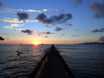 El embarcadero de la roca lleva a la puesta del sol sobre el Océano Pacífico Fotografía de archivo libre de regalías