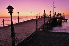 El embarcadero de madera se encendió por resplandor rosado de la salida del sol Fotografía de archivo
