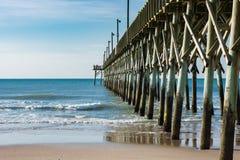 El embarcadero del océano extiende hacia fuera en los cielos azules y el agua Fotografía de archivo