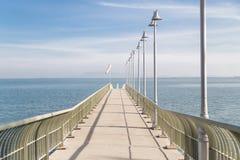 El embarcadero en la costa alcanza hacia fuera para calmar el mar azul Foto de archivo