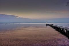 El embarcadero en el lago Garda, sol rosado fijó fotos de archivo libres de regalías
