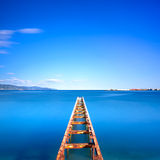 El embarcadero o el embarcadero de madera permanece en un lago azul del océano Exposición larga Imágenes de archivo libres de regalías