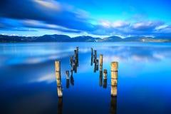 El embarcadero o el embarcadero de madera permanece en un refle azul de la puesta del sol y del cielo del lago Imagen de archivo