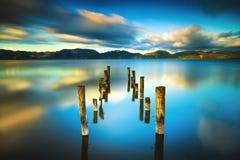 El embarcadero o el embarcadero de madera permanece en un refle azul de la puesta del sol y del cielo del lago Foto de archivo