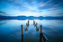 El embarcadero o el embarcadero de madera permanece en una reflexión azul de la puesta del sol y del cielo del lago en el agua. Ve Fotografía de archivo libre de regalías