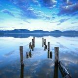 El embarcadero o el embarcadero de madera permanece en una reflexión azul de la puesta del sol y del cielo del lago en el agua. Ve Fotografía de archivo