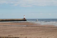 El embarcadero y la playa con la vieja navegación navegan en el Berwick-sobre-tweed imagenes de archivo