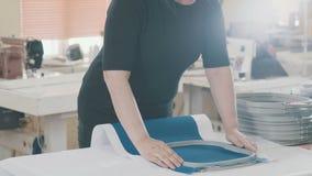 El Embroideress en una fábrica de la materia textil pone la tela en un marco metrajes