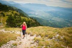 El emigrar - mujer que camina en montañas en un día tranquilo del sumer imágenes de archivo libres de regalías