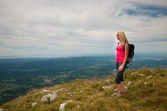 El emigrar - mujer que camina en montañas en un día tranquilo del sumer imagen de archivo