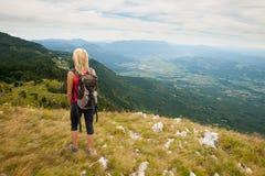 El emigrar - mujer que camina en montañas en un día tranquilo del sumer fotografía de archivo libre de regalías