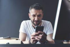El empleado adulto de moda trastornado está sosteniendo smartphone Fotografía de archivo