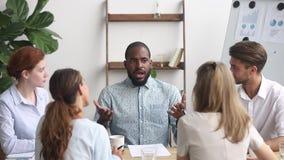 El empleado africano participa las ideas de la producción de la discusión de grupo que solucionan problemas metrajes