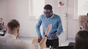 El empleado afroamericano feliz que hace danza divertida del ganador en oficina moderna, da alto-cinco a la cámara lenta del cole metrajes
