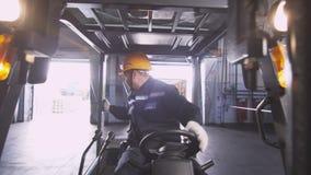 El empleado conduce la carretilla elevadora a lo largo del almacén más allá de la materia almacen de video