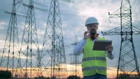 El empleado de la energética está actuando una tableta delante de líneas de transmisión eléctricas metrajes
