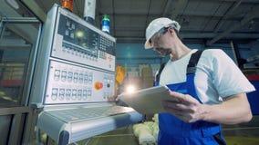 El empleado de la fábrica está actuando una tableta y una consola de supervisión metrajes