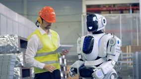 El empleado de la fábrica está comunicando con un humanoid en gestos metrajes