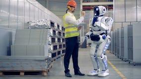 El empleado de la fábrica y un humanoid están comunicando en una instalación de la fábrica almacen de metraje de vídeo