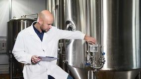 El empleado de los controles de la cervecería el equipo Máquina de funcionamiento del control del trabajador del mantenimiento en almacen de metraje de vídeo